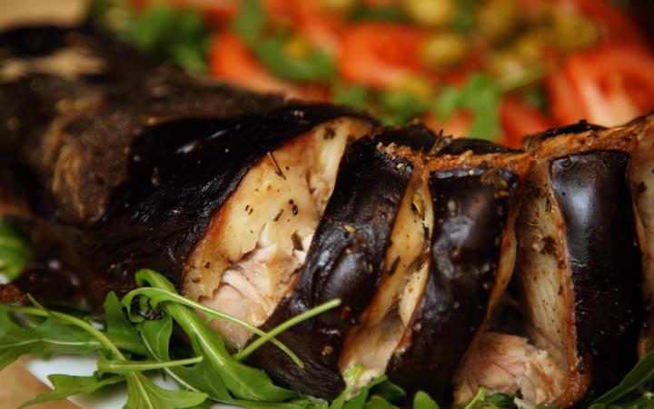 Сом, запеченный в духовке с луком и помидорами